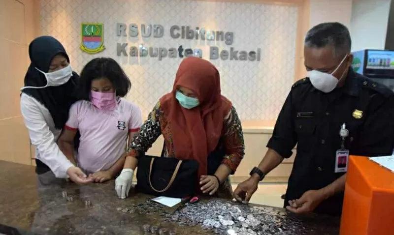Tania Amelinda (15) dan Maulida Lailatul (9) menyumbangkan celengan hasil menyisihkan sebagian uang jajan untuk membantu Rumah Sakit Umum Daerah Kabupaten Bekasi memenuhi kebutuhan alat pelindung diri