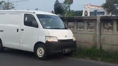 Foto Screenshot, Mobil Minibus warna putih diduga buang sampah di kali Malang.